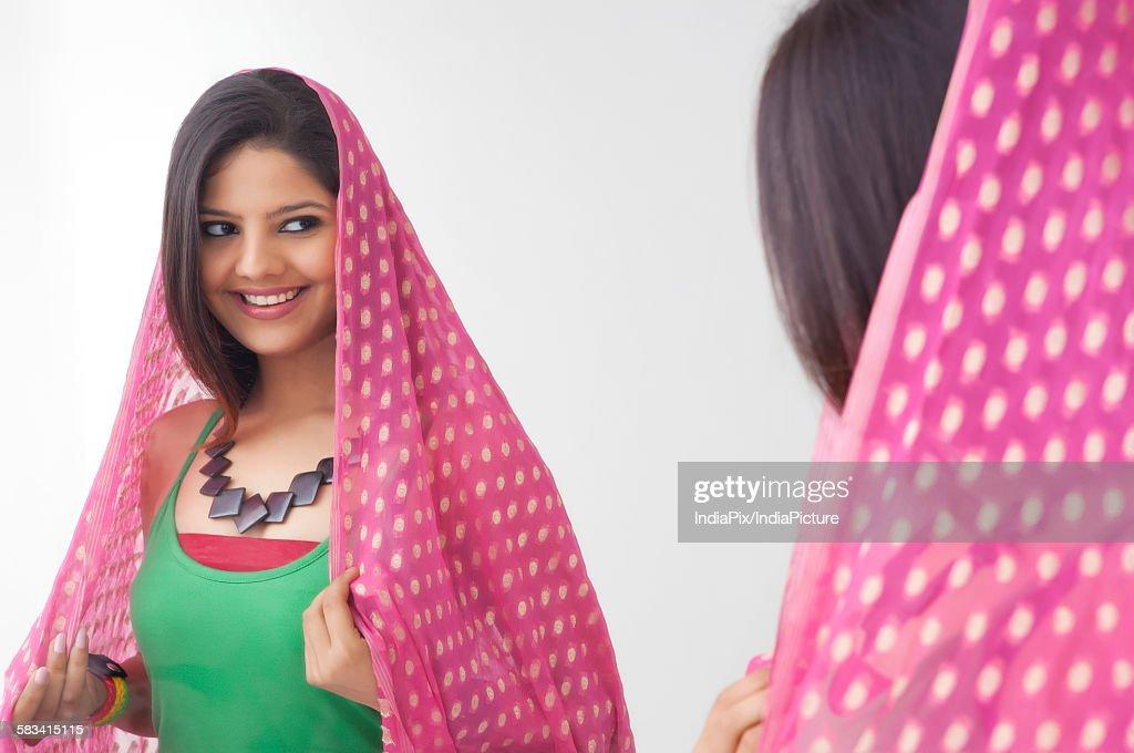 Young woman looking at herself in the mirror : Stock Photo
