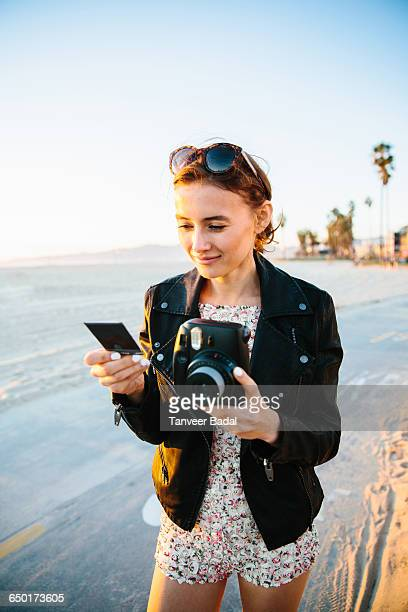 Young woman looking at instant photograph on beach, Venice Beach, California, USA