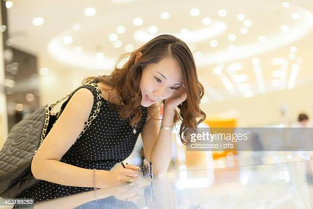 young woman looking at jewelry in shopping mall