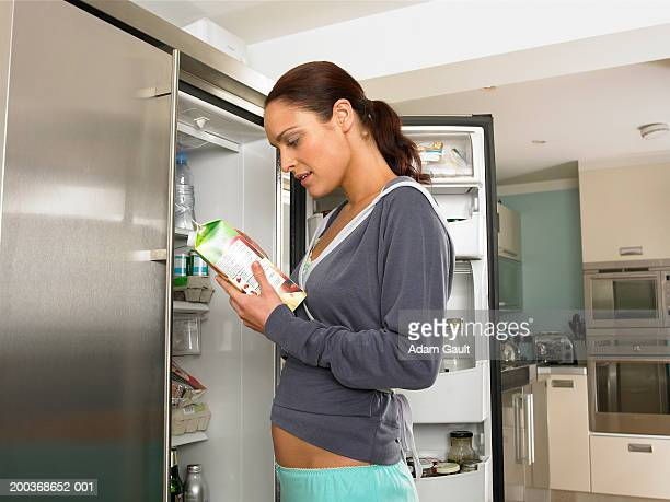 Young woman looking at juice container by fridge