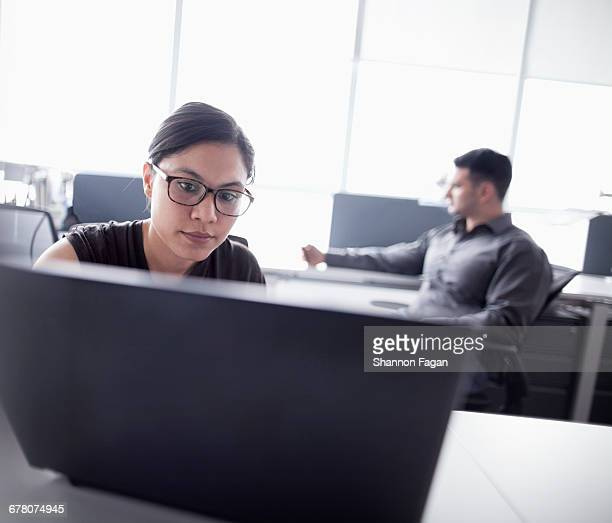 Young woman looking at laptop computer in office