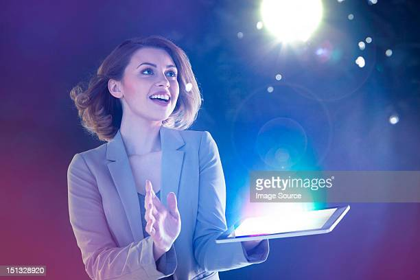 Young woman looking at lights coming from digital tablet