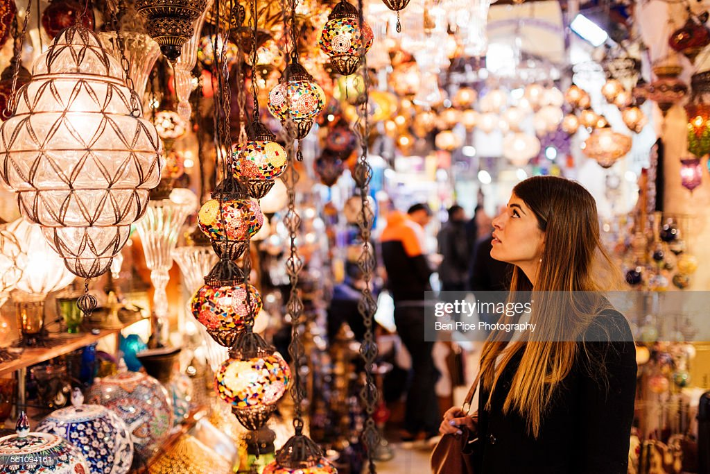 Young woman looking at lights on market stall, Istanbul, Turkey : Foto de stock