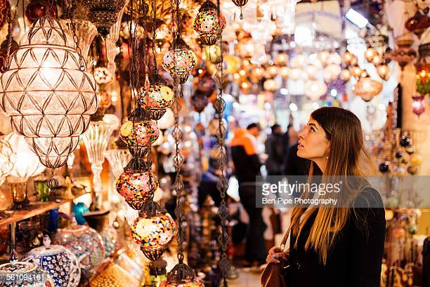 young woman looking at lights on market stall, istanbul, turkey - istanbul photos et images de collection