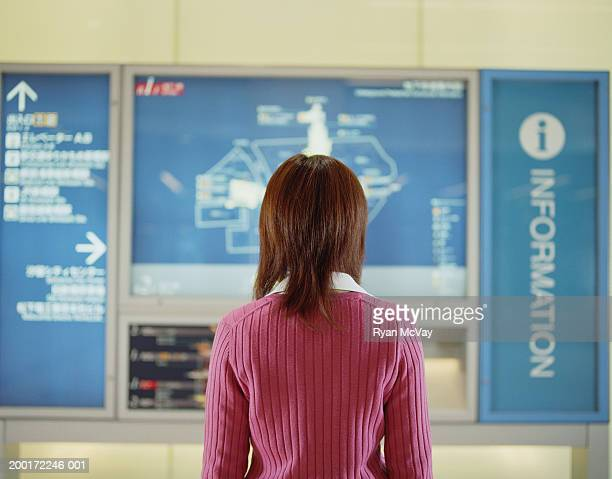 Young woman looking at map in subway station, rear view