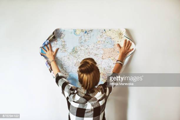 young woman looking at map - world map stock photos and pictures