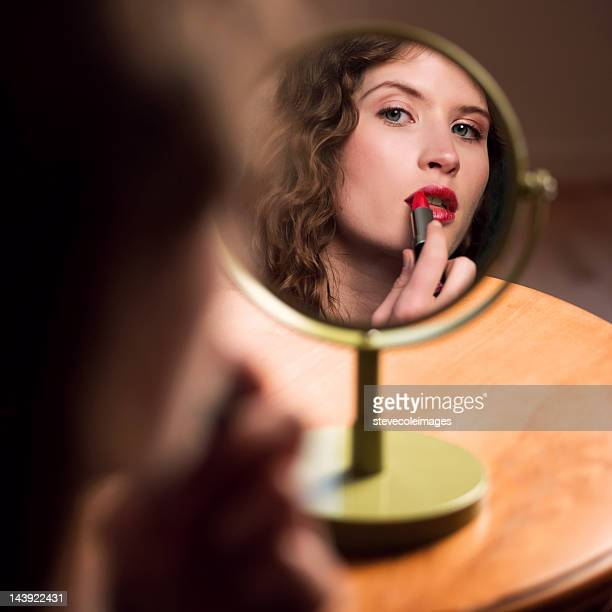 Young Woman Looking At Mirror Applying Lipstick