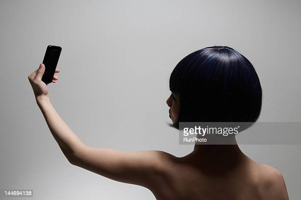 young woman looking at mobile phone - birthday suit stock pictures, royalty-free photos & images