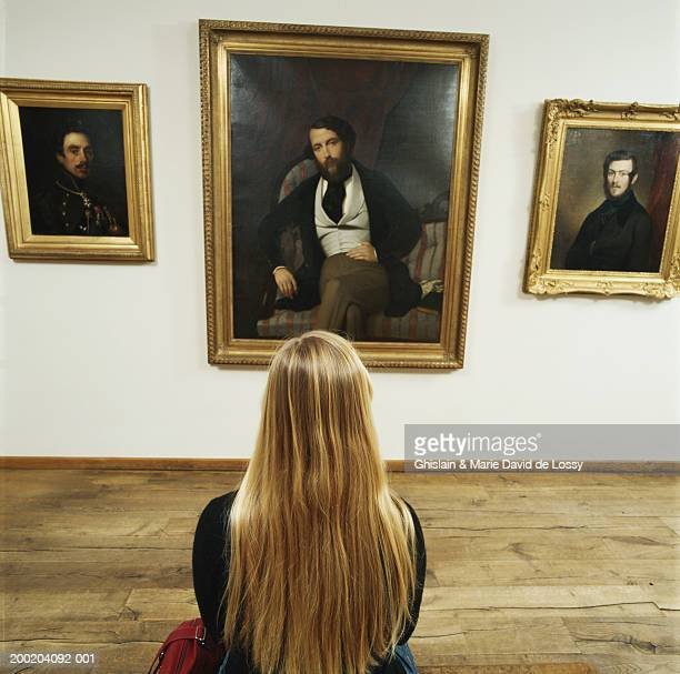 Young woman looking at paintings on wall, rear view
