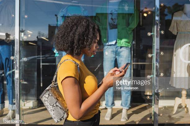 young woman looking at phone outside shop window - retail stock pictures, royalty-free photos & images
