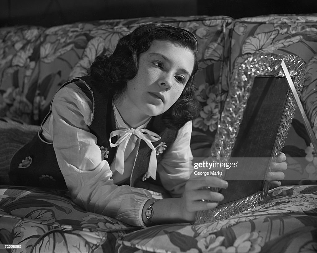 Young woman looking at picture frame : News Photo