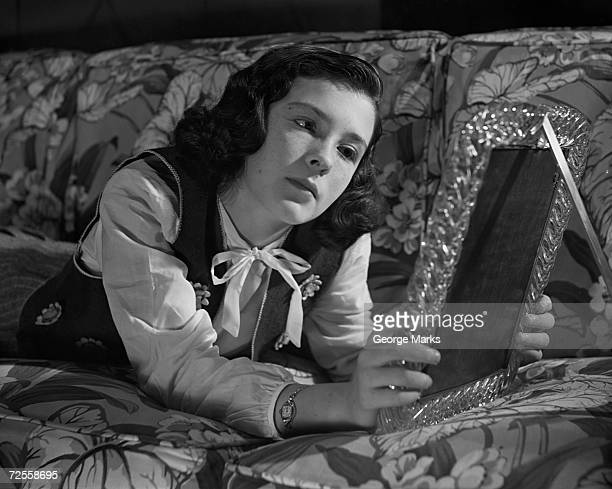 Young woman looking at picture frame