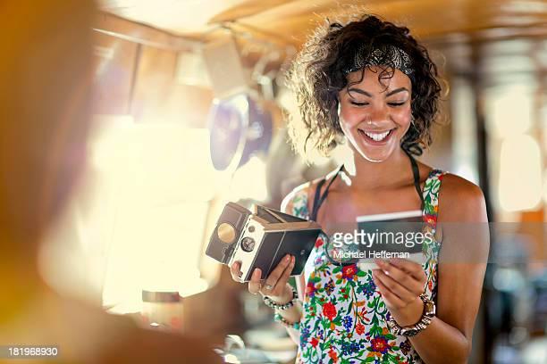 young woman looking at polaroid