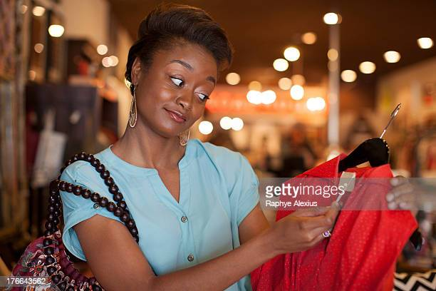 Young woman looking at price tag on red vintage dress