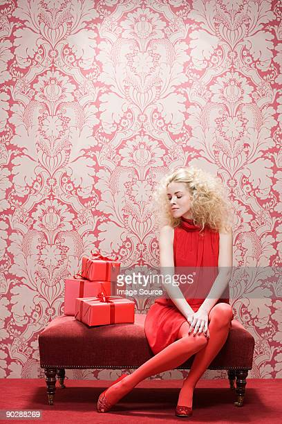 Young woman looking at red gifts