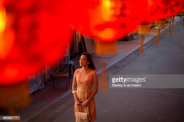 Young woman looking at red lanterns at night.