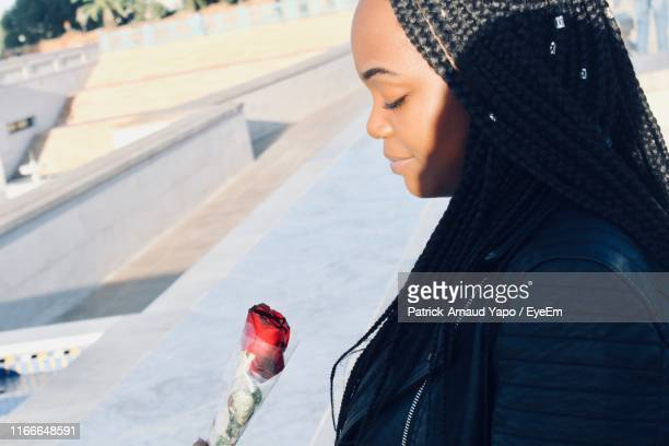 young woman looking at red rose in city - rabat maroc photos et images de collection