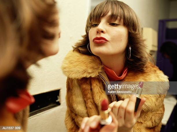 young woman looking at reflection in mirror, holding lipstick - lipstick stock pictures, royalty-free photos & images