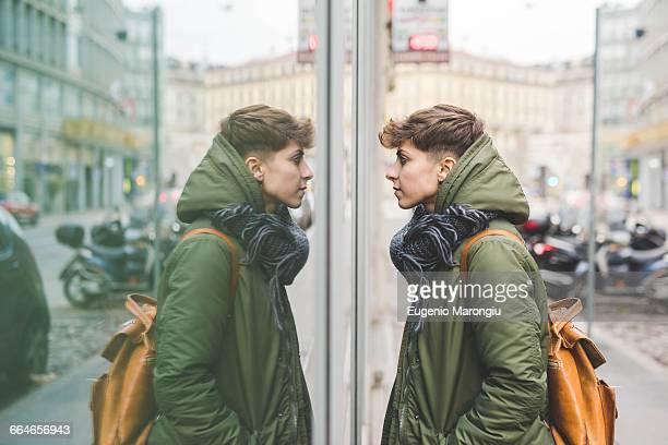 young woman looking at reflection in window, outdoors - simetría fotografías e imágenes de stock