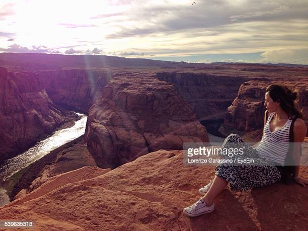 Young Woman Looking At River While Sitting On Rocky Mountains