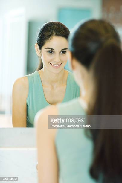 Young woman looking at self in mirror