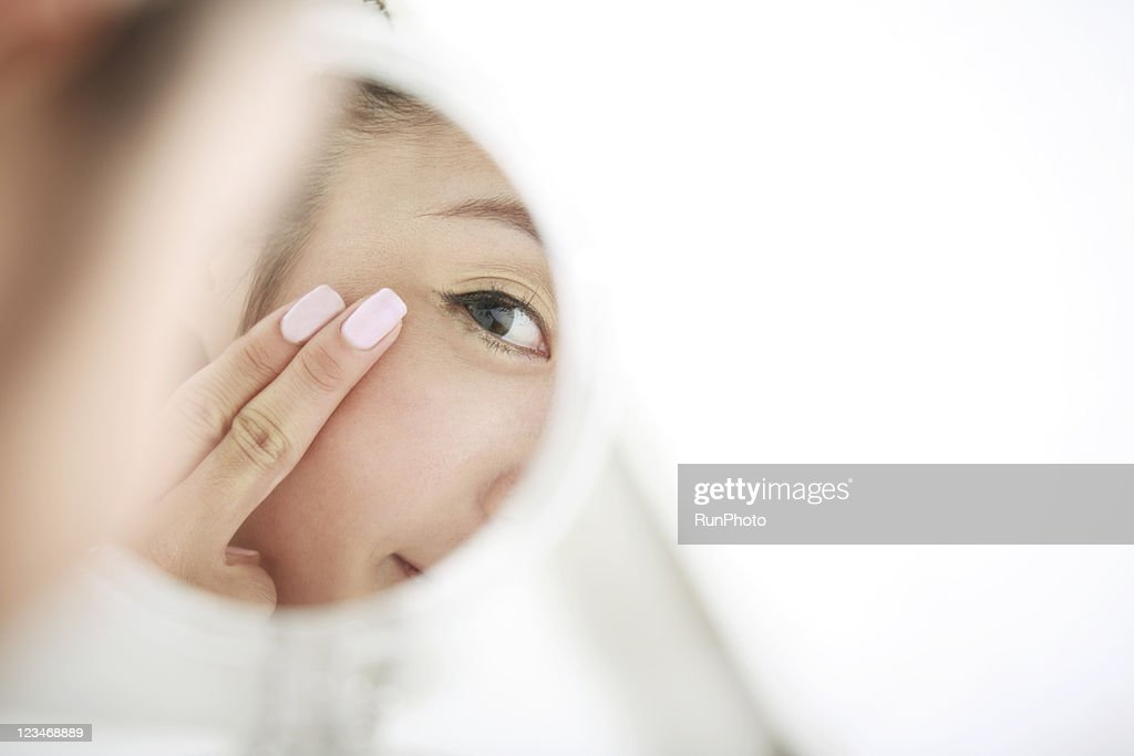young woman looking at self in mirror,skin care : Stock Photo