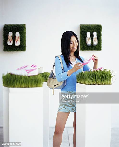 young woman looking at shoe in store - japanese short skirts stock pictures, royalty-free photos & images