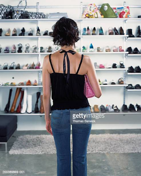 Young woman looking at shoes in retail store, rear view