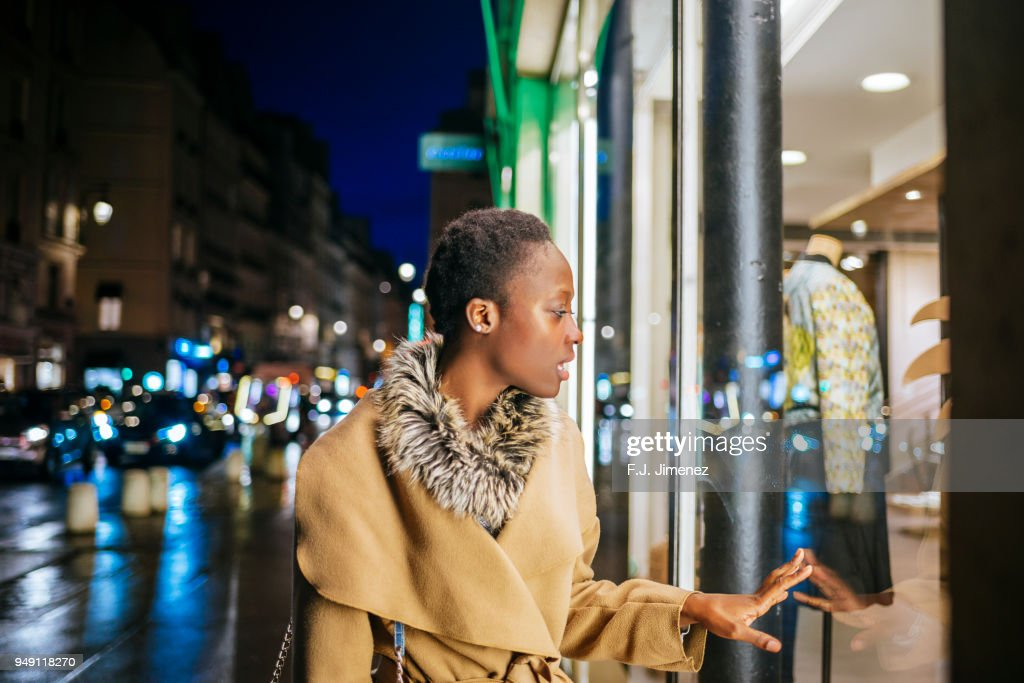 Young woman looking at shop windows through the streets of Paris at night : Stock Photo
