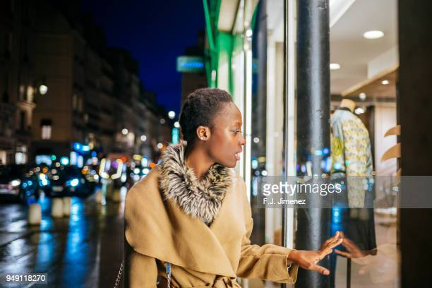 Young woman looking at shop windows through the streets of Paris at night