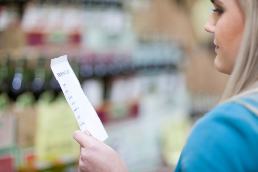 Young woman looking at shopping list in supermarket - gettyimageskorea