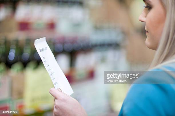 Young woman looking at shopping list in supermarket