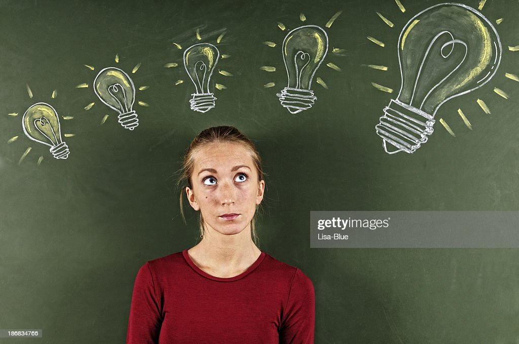 Young Woman Looking at Sketched Light Bulbs : Stock Photo