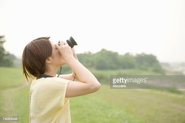 Young woman looking at sky and taking pictures