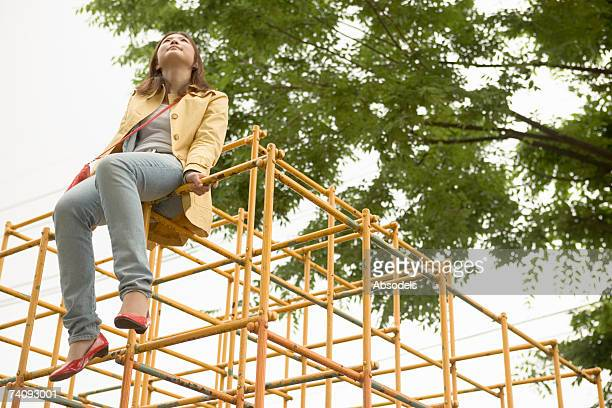 Young woman looking at sky on a jungle gym