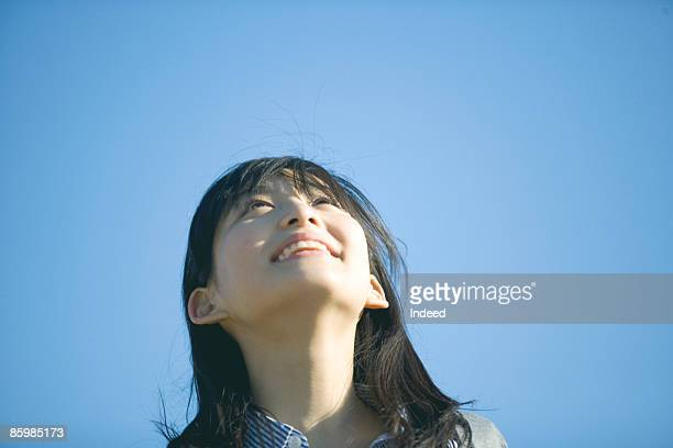 young woman looking at sky - バイタリティ ストックフォトと画像