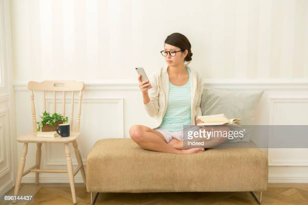 Young woman looking at smart phone in room