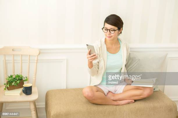 Young woman looking at smart phone on chair