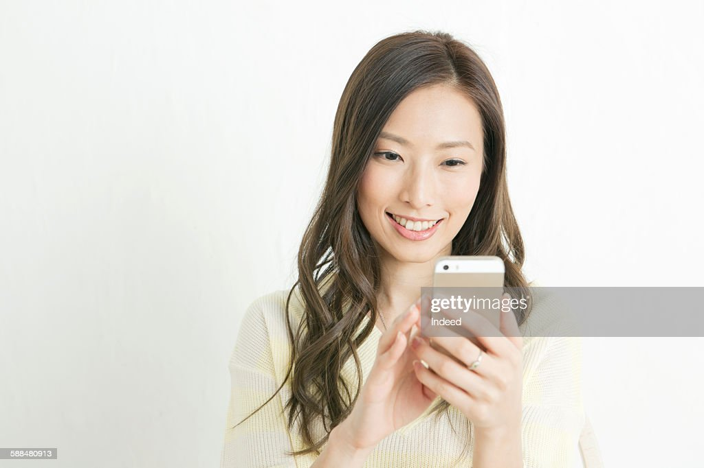 Young woman looking at smart phone : Stock-Foto