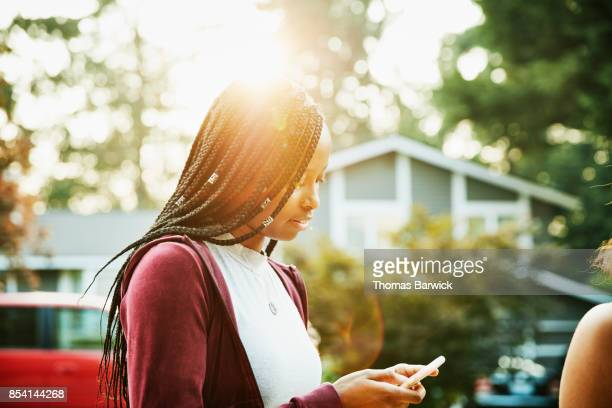 young woman looking at smartphone while hanging out with friends on summer evening - digital native stock pictures, royalty-free photos & images