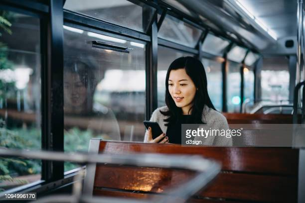 Young woman looking at smartphone while riding tram in the city