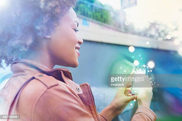 Young woman looking at smartphone with glowing lights coming out