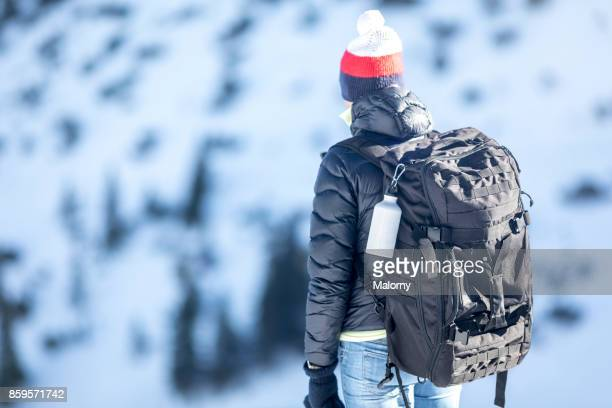 Young woman looking at snow covered mountains
