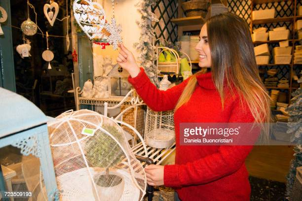 Young woman looking at snowflake christmas decoration in gift shop