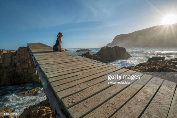 jeune femme regardant le coucher de soleil au bord de la mer - bras de mer caractéristiques côtières photos et images de collection