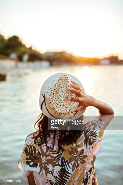Young Woman Looking At Sunset Over Sea