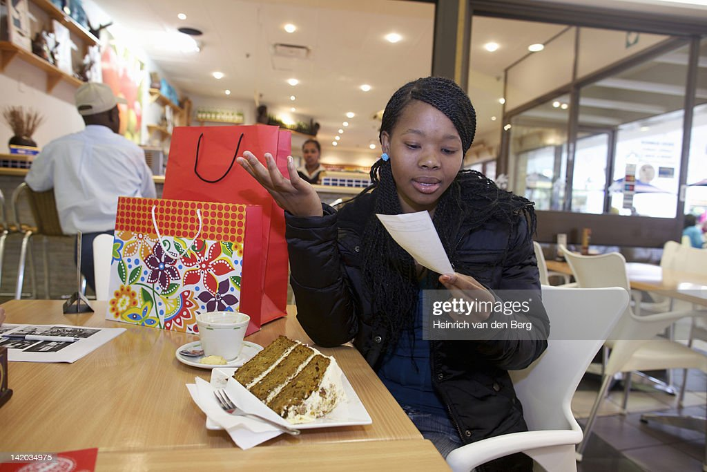 A young woman looking at the bill while sitting at a coffee shop. Pietermaritzburg, KwaZulu-Natal, South Africa : Stock Photo
