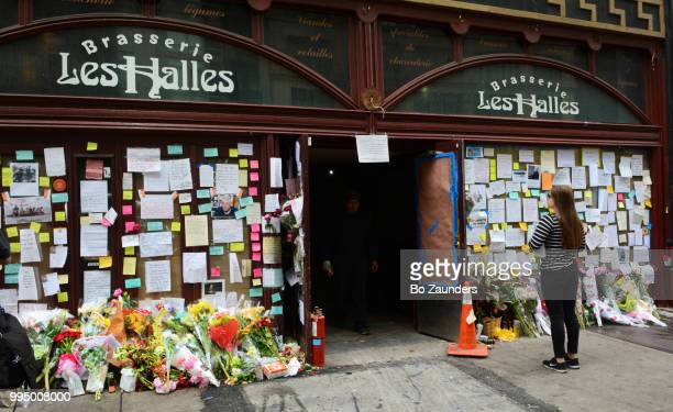 Young woman, looking at the flowers, notes, and photos left in memory of Anthony Bourdain, on display at the closed Brasserie Les Halles in NYC, where Bourdain once worked as an exective chef. where