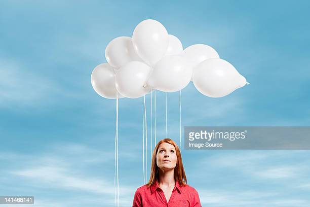 young woman looking at thought bubble made of balloons - thought bubble stock pictures, royalty-free photos & images