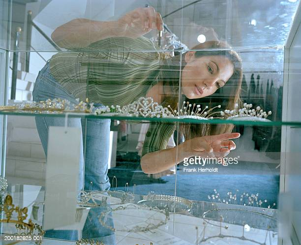Young woman looking at tiaras in glass cabinet, view through glass